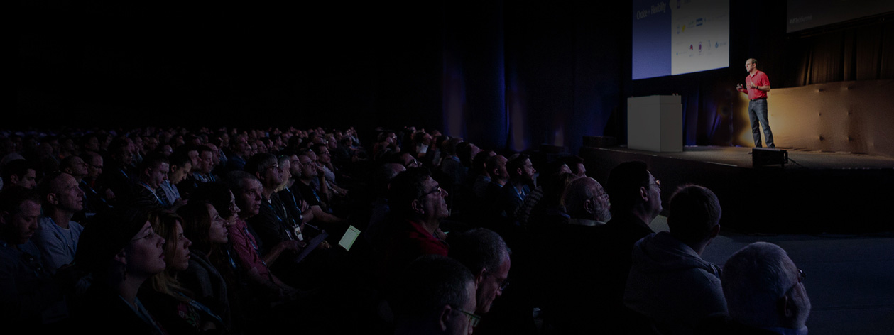 Wide shot of unidentified speaker addressing audience in an auditorium
