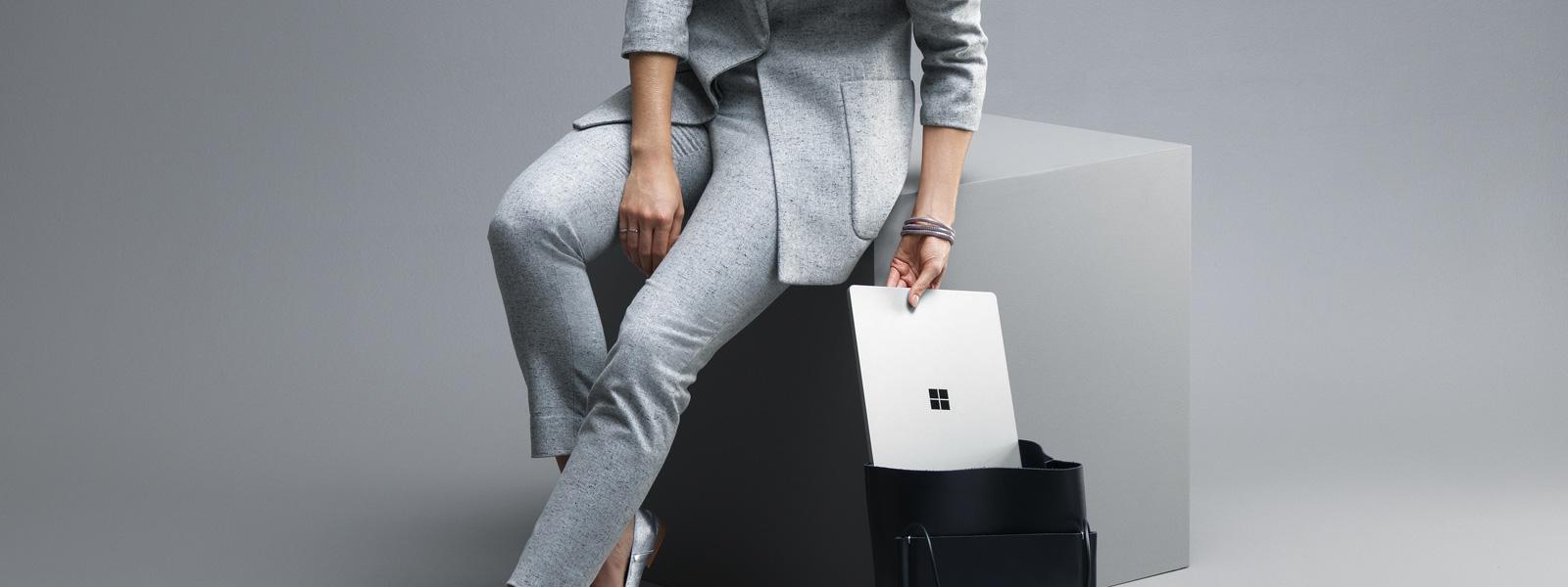سيدة تضع جهاز Surface Laptop البلاتيني في حقيبتها.