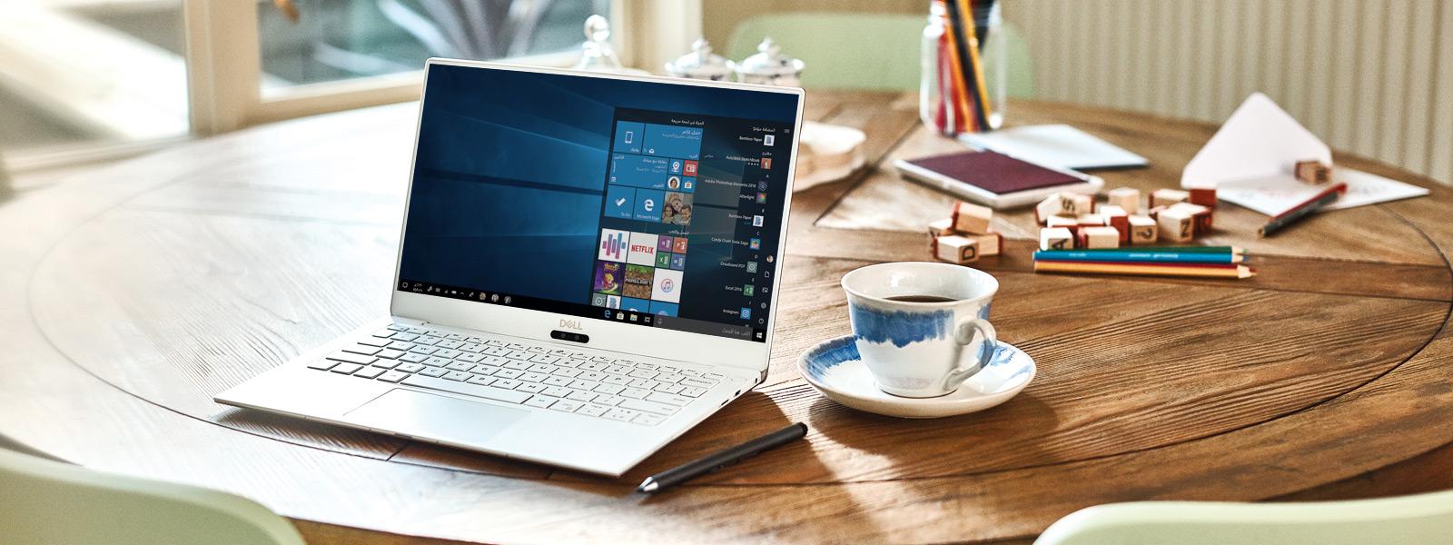 يفتح جهاز Dell XPS 13 9370 على طاولة بشاشة بدء نظام Windows 10.