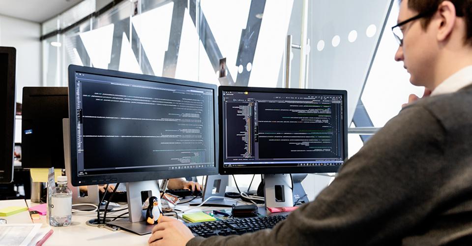 صورة لشخص في مساحة مكتب مشتركة يعمل في مكتب به شاشتين كبيرتين تعرضان معلومات