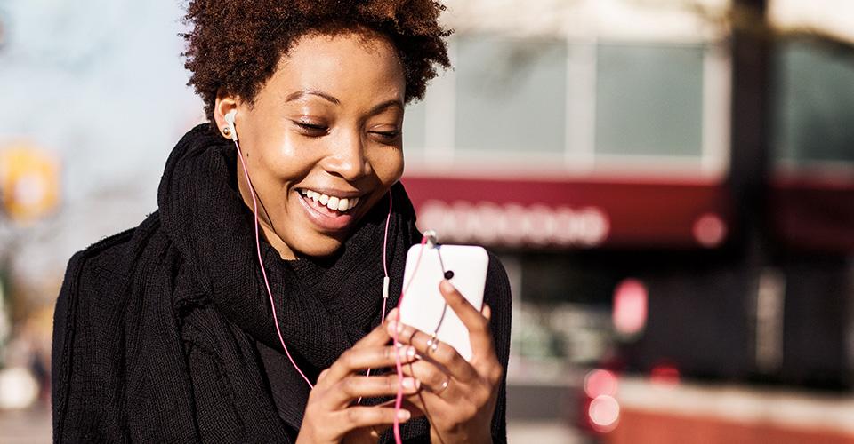 شخص ذو إطلالة رسمية، بالخارج، يستخدم جهازه المحمول ويرتدي سماعات الأذن