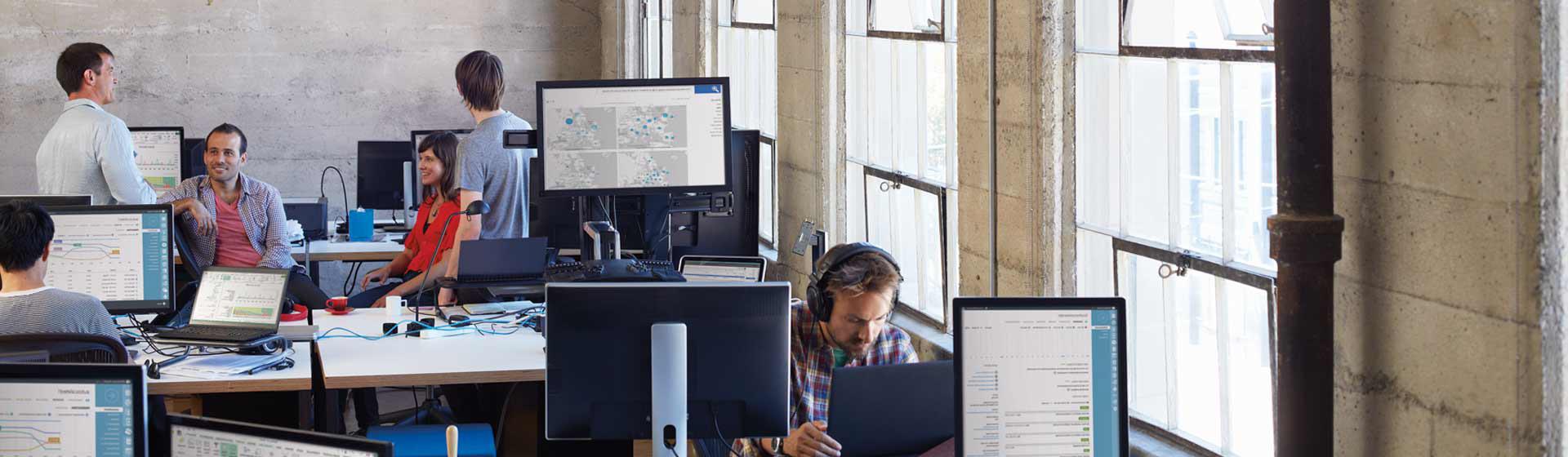 مجموعة من زملاء العمل يجلسون ويقفون حول مكاتبهم في مكتب مكتظ بأجهزة كمبيوتر يتم تشغيل Office 365 عليها
