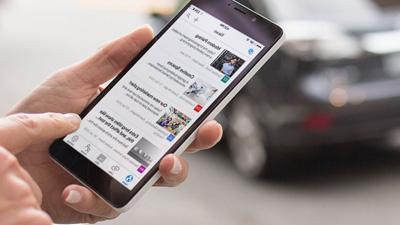 أيادٍ موضوعة على هاتف ذكي يُشغّل SharePoint