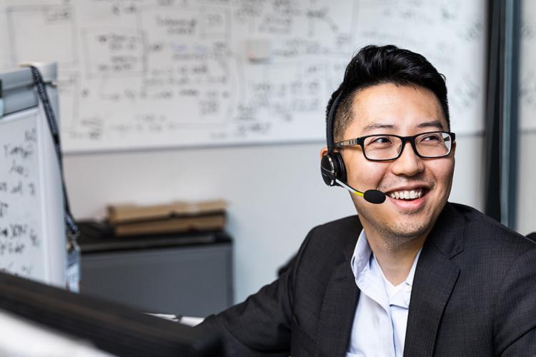 شخص يرتدي نظارة يجلس على مكتب، ويرتدي سماعة الرأس