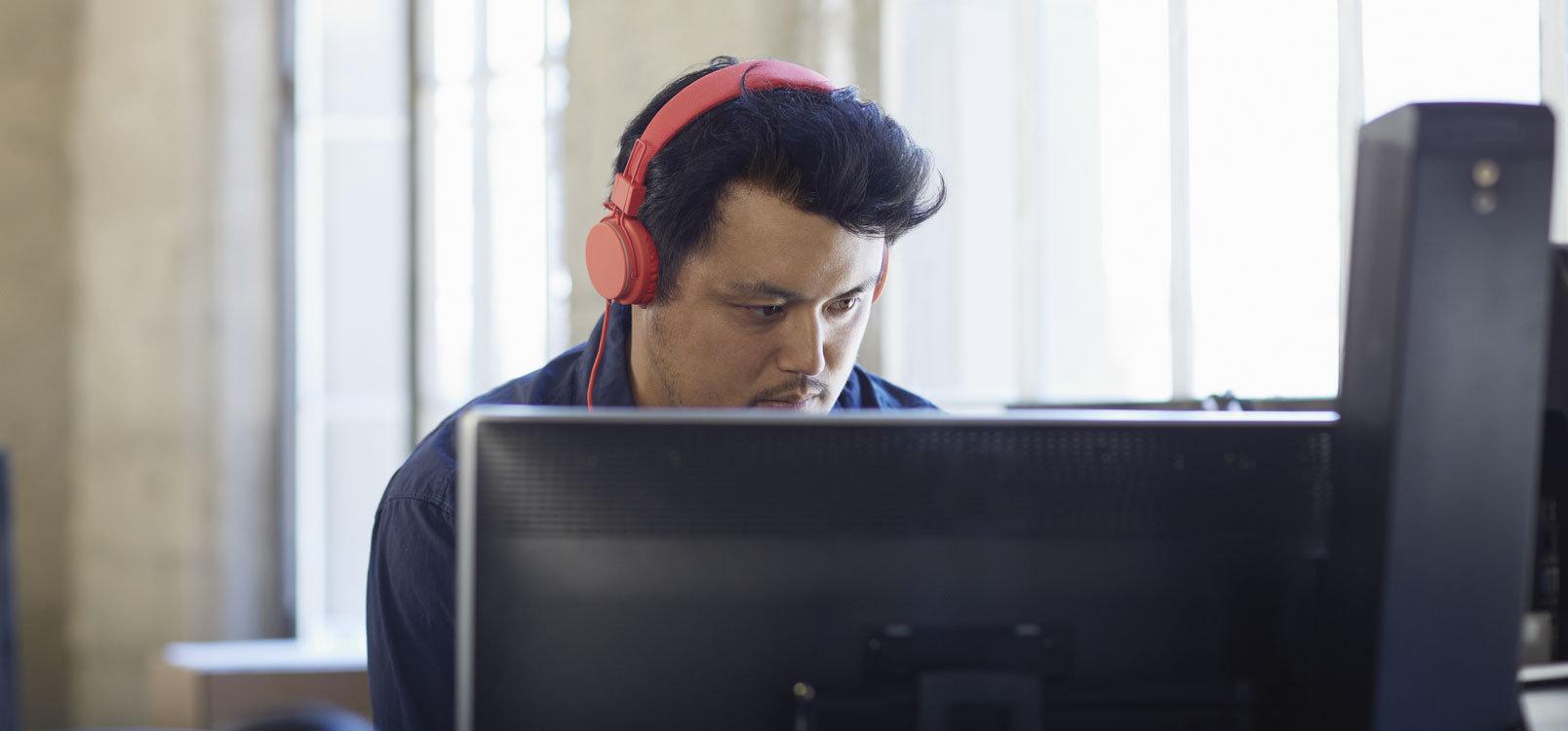 شخص يرتدي سماعات رأس ويعمل على كمبيوتر سطح مكتب مستخدماً Office 365 لتبسيط تكنولوجيا المعلومات.