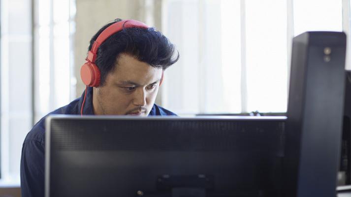 شخص يرتدي سماعات الرأس ويعمل على كمبيوتر سطح المكتب مستخدماً Office 365 لتبسيط تكنولوجيا المعلومات.