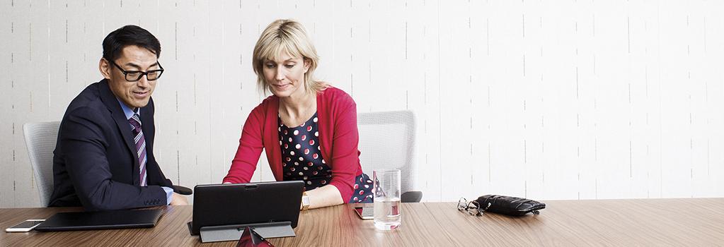 رجل وامرأة ينظران إلى جهاز كمبيوتر على طاولة في بيئة عمل