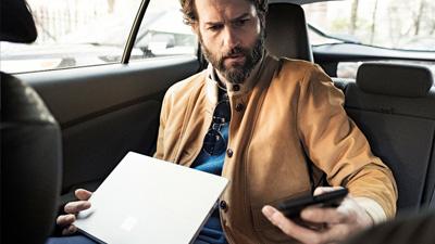 شخص في سيارة يستخدم جهاز كمبيوتر محمول مفتوح وينظر في جهازه المحمول