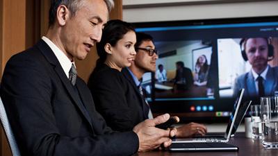 ثلاثة أشخاص في مؤتمر عبر الفيديو في قاعة المؤتمرات