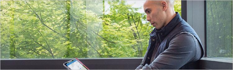 رجل ينظر إلى كمبيوتر لوحي