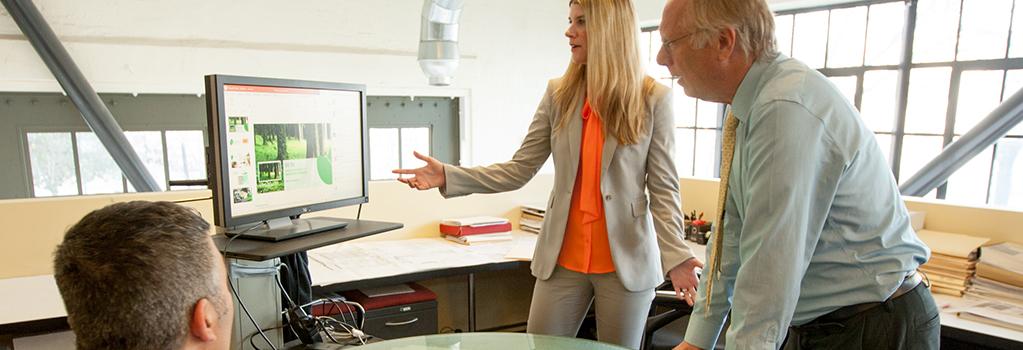 موظفون يناقشون معلومات على جهاز عرض