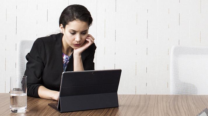 امرأة تجلس على طاولة وتعمل على كمبيوتر لوحي