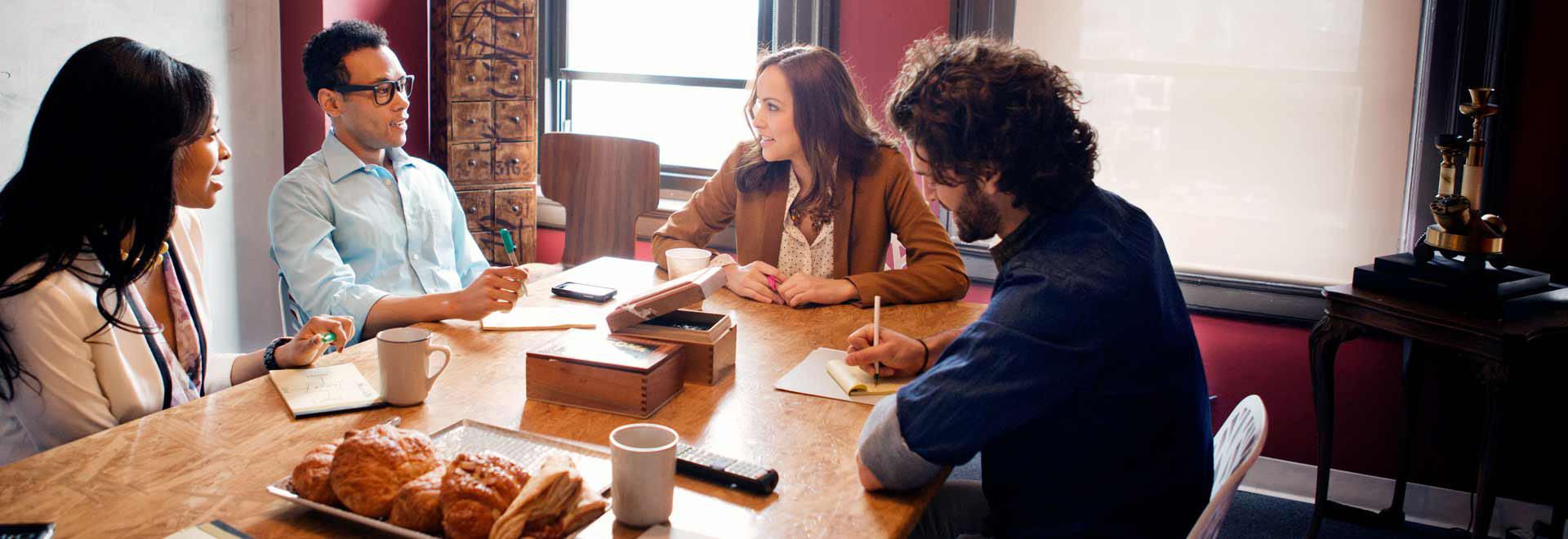 أربعة أشخاص يعملون في مكتب ويستخدمون Office 365 E3.