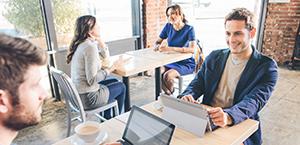 رجلان يجلسان حول طاولة في الكافتيريا ويتعاونان في العمل باستخدام أجهزة الكمبيوتر اللوحية، تعرّف على Microsoft Dynamics CRM.