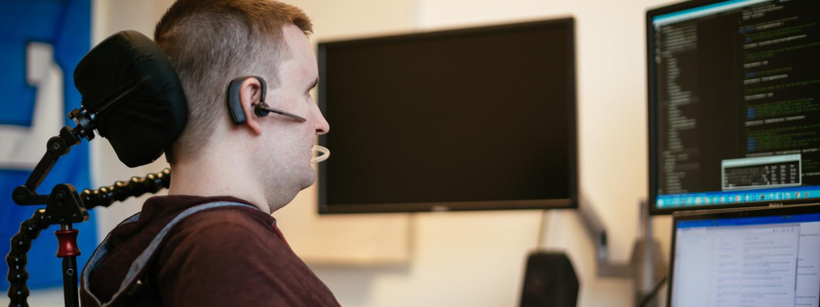 Мъж, седящ на бюро и използващ помощна хардуерна технология, за да работи на компютър с Windows 10 с контролите за управление с поглед