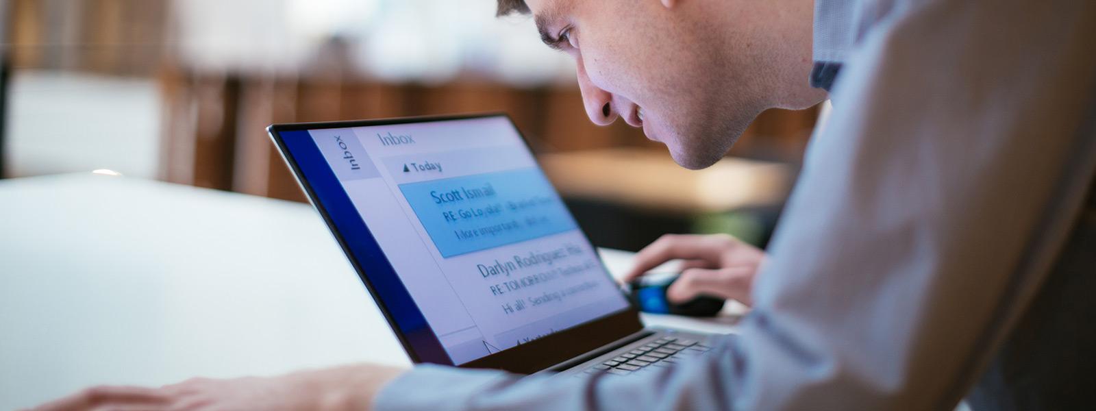 Muž pracující na svém počítači se systémem Windows 10 se snadno čitelným velkým textem zobrazeným na obrazovce.