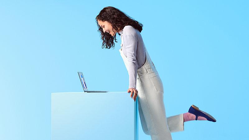 Osoba hledící na přenosný počítač s Windows 11