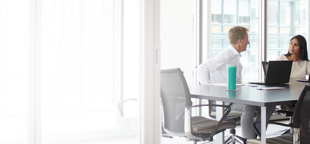Dva zaměstnanci pracující v konferenční místnosti s Office 365 Enterprise E3 na přenosných počítačích.