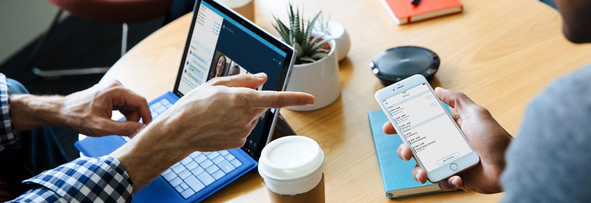 Dvě osoby u stolu, jedna s telefonem a druhá s přenosným počítačem, používající Skype pro firmy