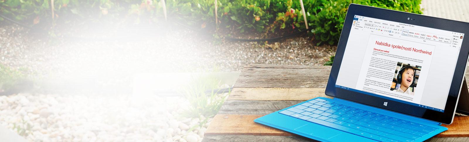 Pracovník píšící na klávesnici s dokumentem aplikace Word na obrazovce