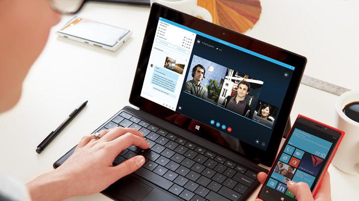 Osoba pracující snotebookem atelefonem, na kterých je Online Skype pro firmy