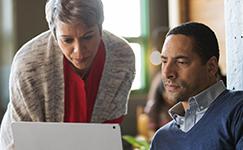 Muž a žena se dívají na přenosný počítač