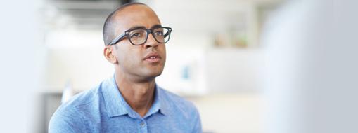 Muž sedí v kanceláři a čte si příběhy zákazníků o používání Projectu v organizacích.
