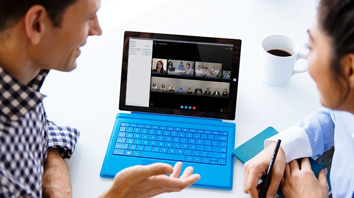 Muž a žena používají přenosný počítač k videokonferenci s jinými uživateli