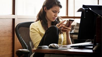 Žena u pracovního stolu hledí do mobilního zařízení
