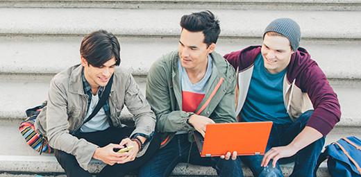 Tři chlapci sedící venku na schodech, jeden stelefonem, druhý snotebookem