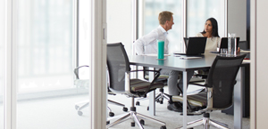 Muž a žena pracující u konferenčního stolu na přenosném počítači s Office 365 Enterprise E3.