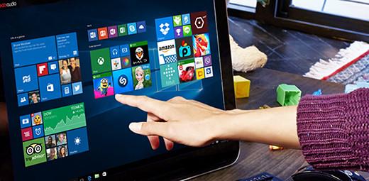 Ruka ženy, která se chystá dotknout dlaždice aplikace na počítači sdotykovou obrazovkou