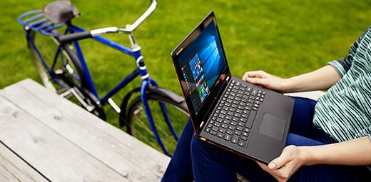 Osoba sedící na piknikovém stole, na kolenou notebook sWindows10