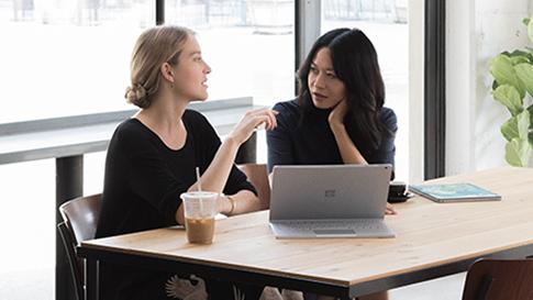 To kvinder sidder på en café med en SurfaceBook2 i visningstilstand foran sig.