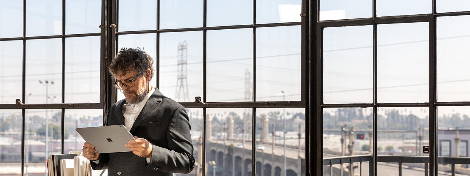 En mand, der står ved et vindue og kigger på sin Surface Book 3-tablet