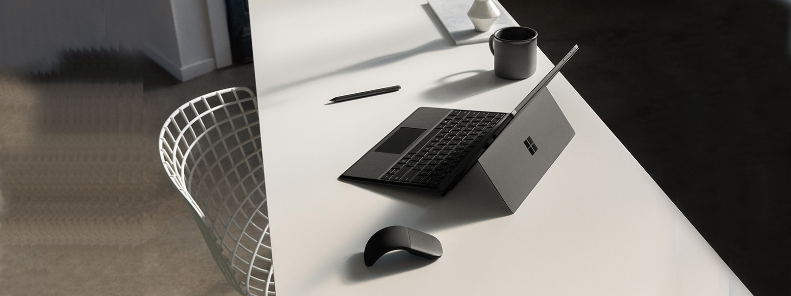 Surface Pro 6 på et skrivebord i laptoptilstand med Surface Pro Type Cover, Surface Pen og Surface Arc Mouse