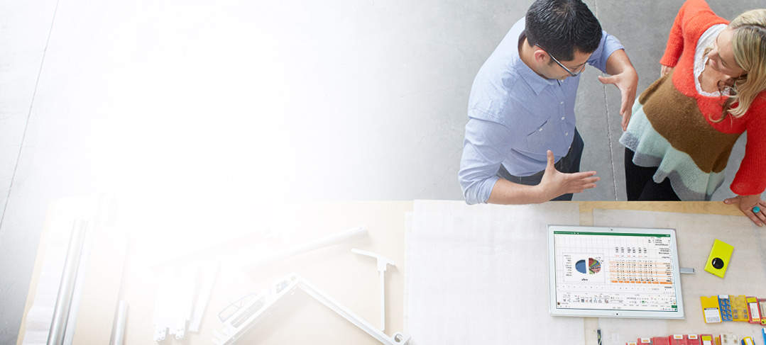 En mand og en kvinde står ved et tegnebord og bruger Office 365 ProPlus på en tablet.