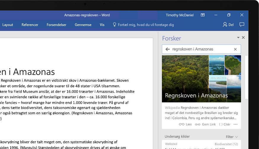 En bærbar computer, der viser et Word-dokument og et nærbillede af funktionen Researcher med en artikel om regnskoven i Amazonas