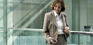 En kvinde, der kigger ned på sin telefon, læs om Exchange Online-arkivering-funktioner og -priser