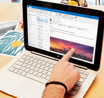 En bærbar computer med et eksempel på en Office 365-mail med brugerdefineret formatering og et billede.