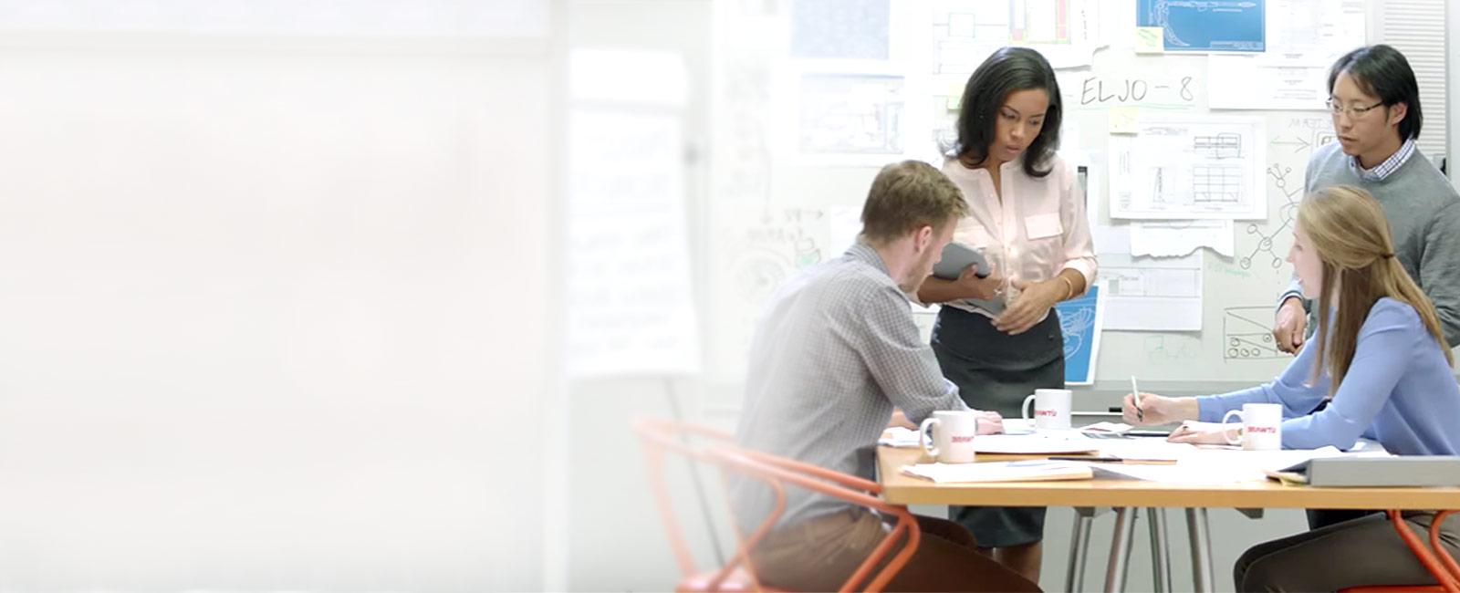 To stående personer og to personer, der sidder ved et bord fyldt med dokumenter foran et whiteboard.