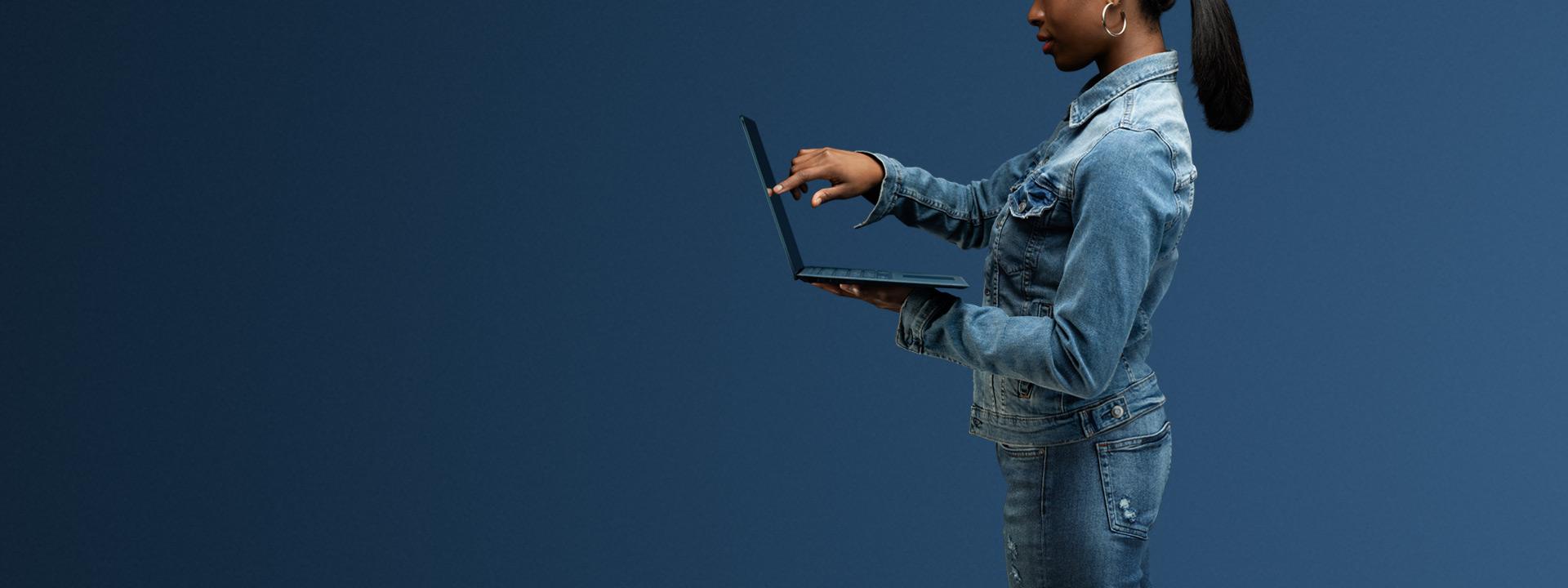 En pige holder Surface laptop 2, mens hun rører skærmen