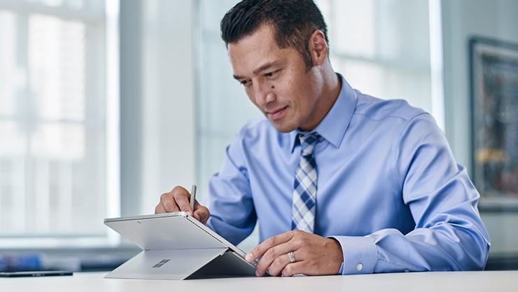 Mand, der skriver på Surface Book
