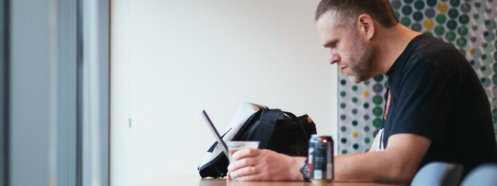 Ein Mann sitzt mit seinem Windows 10-PC an einem Tisch und arbeitet
