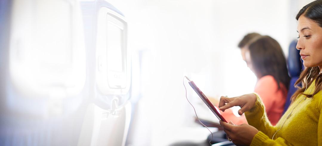 Frau im Zug, die Office 365 auf einem Tablet verwendet, um mit anderen an Dokumenten zusammenzuarbeiten.