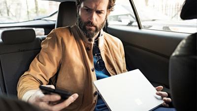 Eine Person, die mit geöffnetem Laptop in einem Auto sitzt und auf ihr Mobilgerät schaut