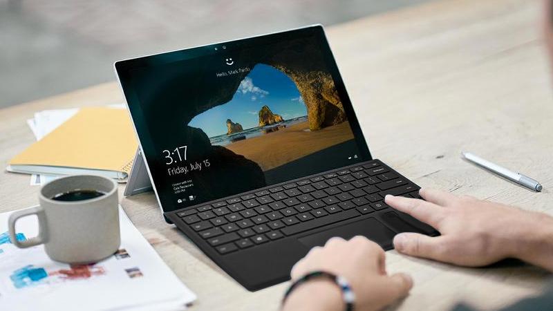 Person an Schreibtisch nutzt Fingerabdrucksensor, um sich bei Surface Pro 4 anzumelden.