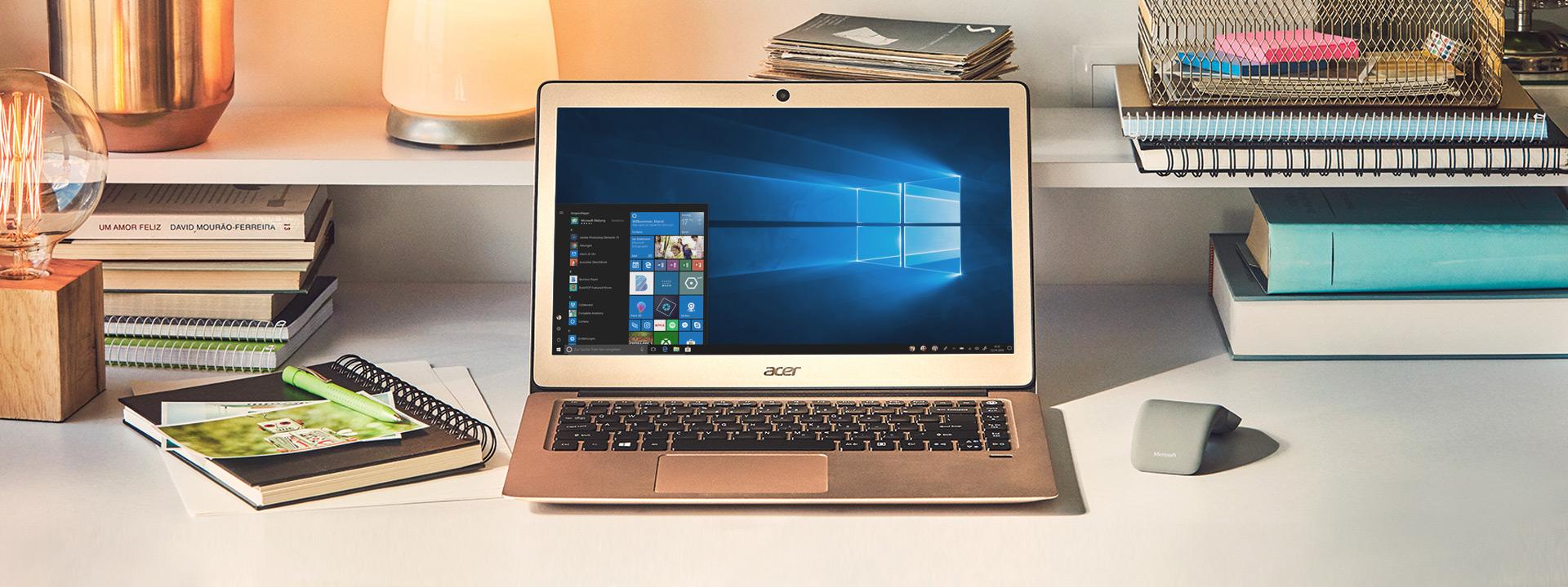 Ein Laptop von Acer und eine Maus befinden sich auf einem Schreibtisch, daneben liegen Bücher und Notizblöcke.