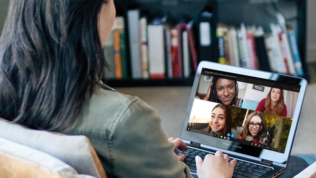 Foto über die Schulter einer Frau, die über Skype auf ihrem Laptop mit Freunden kommuniziert
