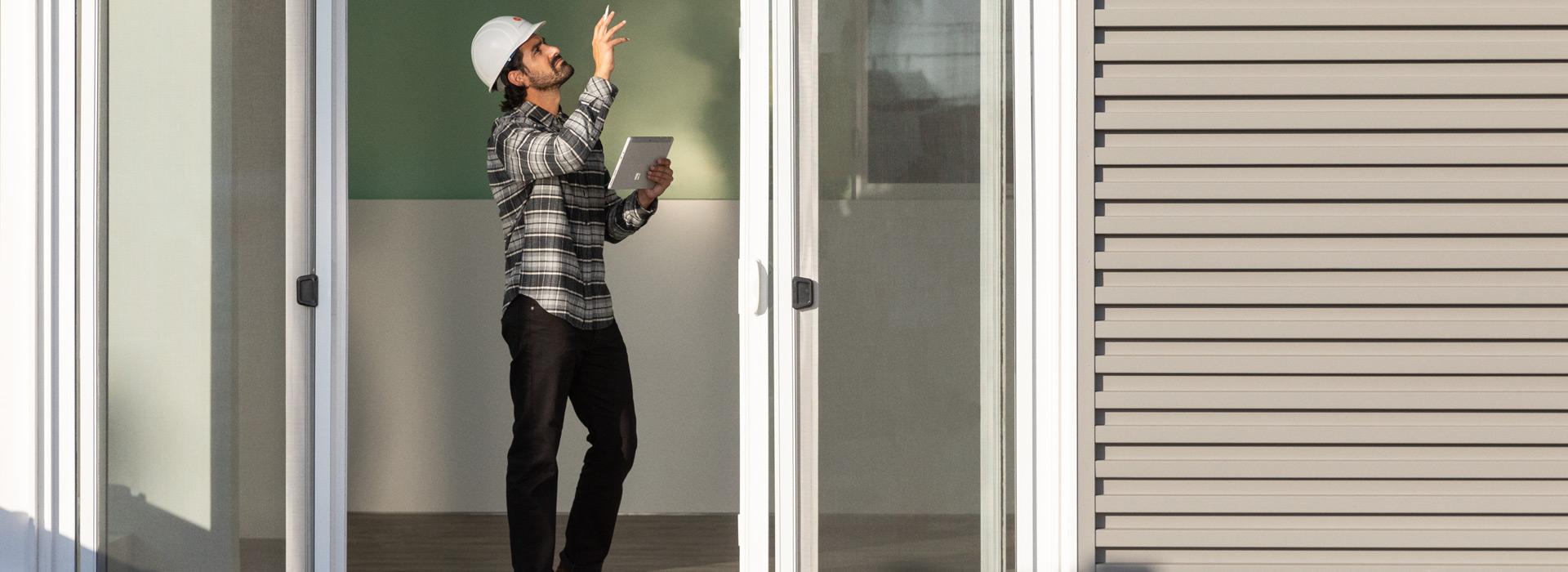 Ein Arbeiter mit einem Schutzhelm in einem Wohngebiet hält ein Surface Go 2 im Tablet-Modus